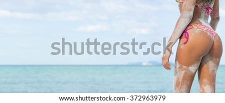 Sexy sandy woman buttocks on the sea background. Wide banner.