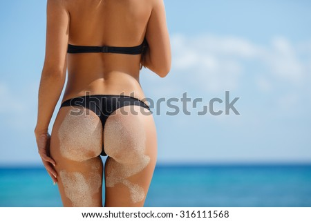 Sexy sandy woman buttocks on tropical beach background near ocean. close up outdoor shot of young woman in white bikini, sunbathing at sea shore. Black bikini on ocean background