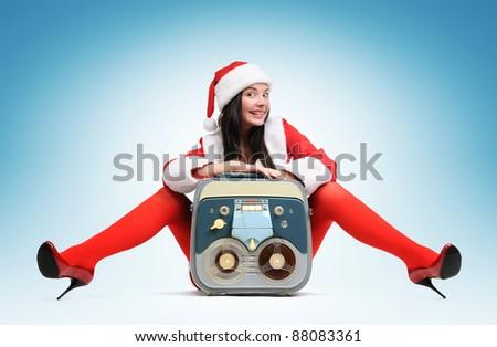 Sexy Santa girl with vintage tape recorder - stock photo