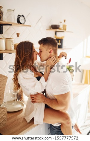 Sexy sensual couple kissing and embracing each other indoors in the kitchen.