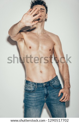 sexy shirtless man in jeans gesturing and posing on grey