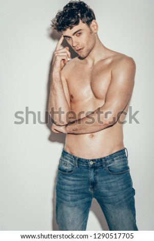 sexy shirtless man in jeans posing on grey