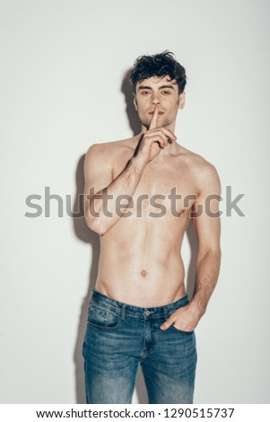 sexy shirtless man in jeans showing silence symbol while posing on grey