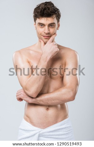 sexy shirtless man thinking in towel isolated on grey