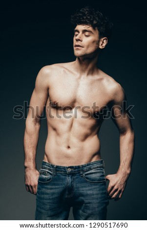 sexy shirtless muscular man in jeans posing isolated on dark grey