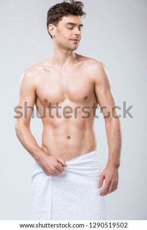 sexy shirtless smiling man posing in towel isolated on grey