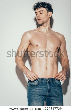 sexy shirtless stylish man in jeans posing on grey