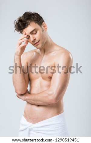 sexy shirtless thoughtful man posing in towel isolated on grey