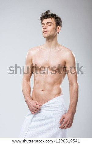 sexy shirtless young man posing in towel isolated on grey