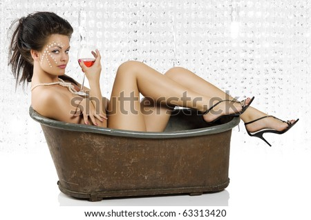 sexy shot of beautiful naked girl sitting in an old fashion bathtub with a glass of red wine
