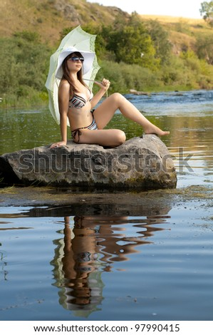 sexy slenderness beautifully girl standing on river, outdoor with  sunshade