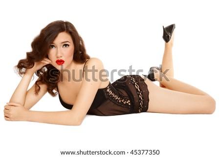 Sexy slim girl in black lingerie lying on white background