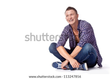 sexy smiling handsome sitting man posing in casual jeans and unbuttoned shirt