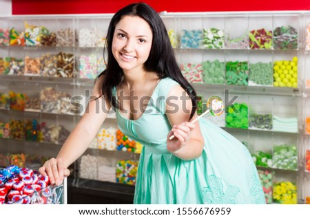 sexy smiling woman posing in the store with lolly on the background of counters with sweets