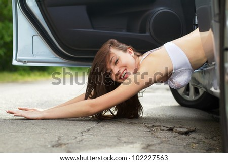 Sexy smiling young woman lying on the road
