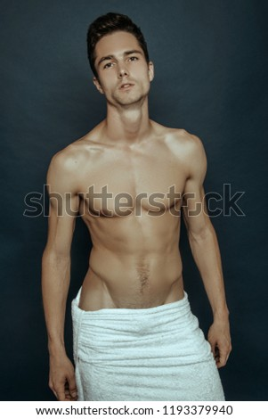 Sexy sport muscle guy with white towel on blue isolated font background