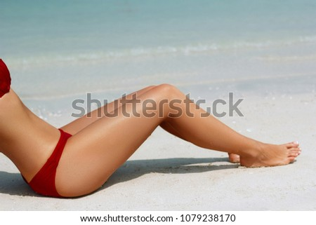 Sexy suntan bikini woman legs relaxing lying down on white sand beach . Beauty skincare sun aging protection body care of tanned skin. Epilation laser or shaving concept. summer vacation.Skincare. #1079238170