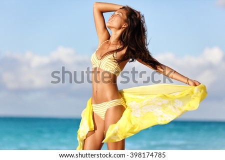 Sexy suntan woman relaxing enjoying sunset on beach with beachwear cover-up wrap showing slim bikini body for weight loss and skin care epilation concept. Asian model sunbathing during summer holiday.