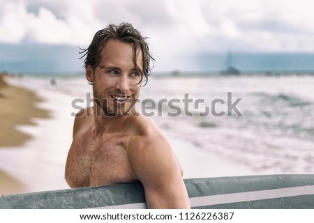 Sexy surfer surfing man with surfboard. Handsome young male athlete holding surf board with wet hair on summer beach sport holiday. Sports travel destination. Surfing lifestyle.
