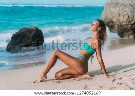 Sexy tanned girl in swimsuit sits on sandy beach background of ocean. Beautiful model sunbathes and rests on tropical island. Concept bikini, summer, tan, travel, swimwear, body #1274052169