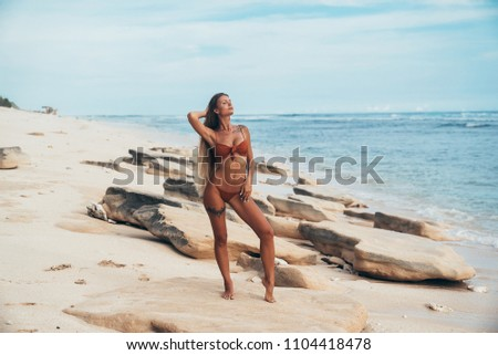 Sexy tanned model with a smooth skin and an even tan rests on a blue beach with white sand. Rest, travel, beach, summer concept. #1104418478