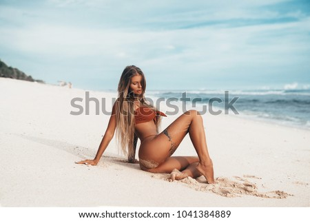 Stock Photo Sexy tattooed young girl in red swimsuit posing on the beach. Beautiful blonde woman with long hair relaxing at the ocean. Concept of sporty model, swimwear