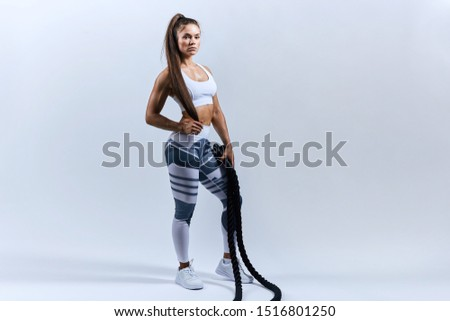 sexy tired sportswoman after battle rope workouts on white background. Attractive female athlete taking rest after fitness training at gym, full length photo. copy space