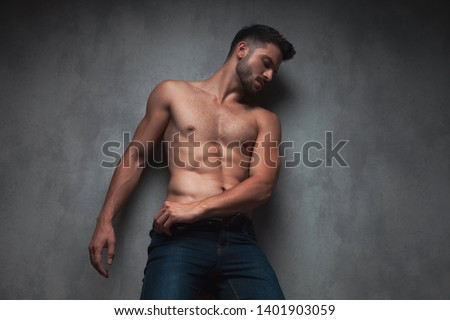 Sexy topless guy looking to the side and adjusting his jeans while leaning against gray studio background