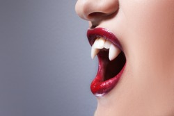 Sexy vampire. Women's lips with red lipstick. Screaming mouth with vampire fangs, copy space