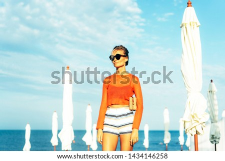 Sexy vogue catwalk look of a gorgeous woman. Blonde in sunglasses, wearing shorts and red sweater on a contrasting blue background of the sea and sky. Beach area with white umbrellas. Summer dresscode