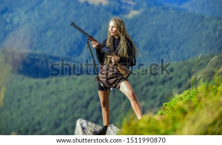 Sexy warrior. She is warrior. Warrior mountains landscape background. Amazon legendary race of female warriors. Hunting season. Woman attractive long hair pretty face hold rifle for hunting.