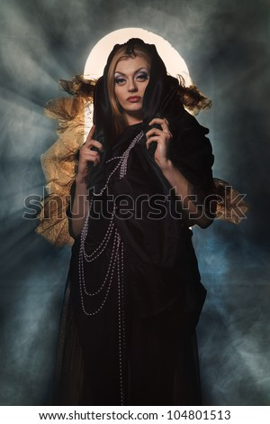 Sexy witch dressed up in black dress covered in smoke