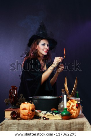 Sexy witch on a dark background making potion looking to the smoke