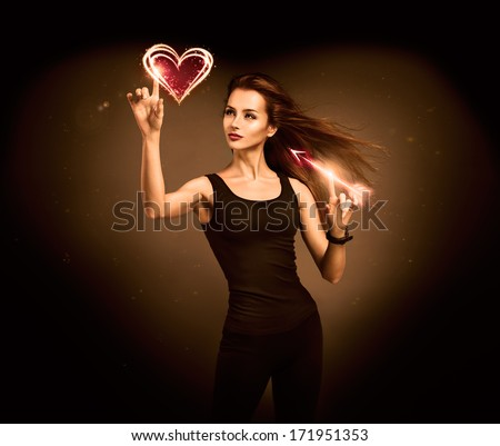 Sexy Woman Aiming to the Glowing Heart with an Arrow on Dark Background. Fantasy Cupid Concept for Valentine's Day.