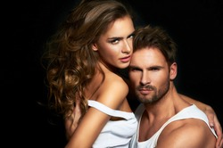 Sexy woman and man in intimacy relations - fashionable couple posing at studio