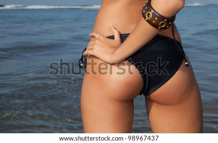sexy woman back with black lingerie on seashore