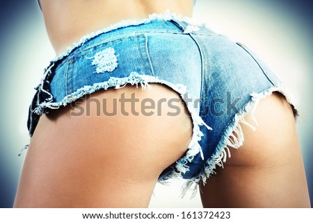 Sexy woman body in jean shorts. The model is back. Great ass. On a blue background.
