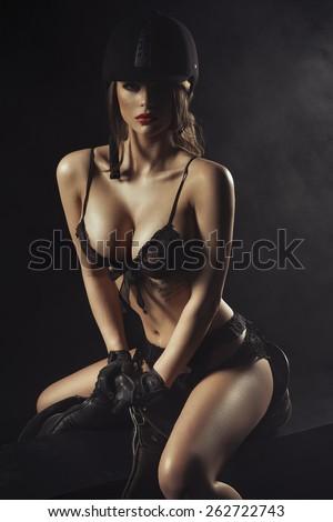 Sexy woman body with saddle and helmet like jockey