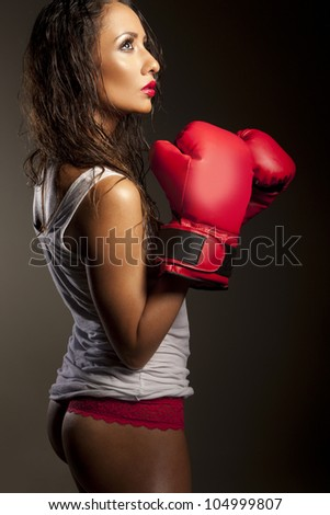 Sexy woman boxer with her hair damp from perpiration pausing during training showing her cute bum
