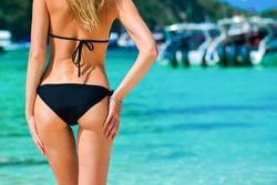 Sexy woman buttocks on tropical beach background near ocean. close up outdoor shot of young woman in black bikini, sunbathing at sea shore. Black bikini on ocean background