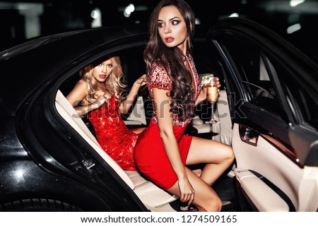 Sexy woman couple in the car. Hollywood star. Fashionable pair of elegant people at night city street.