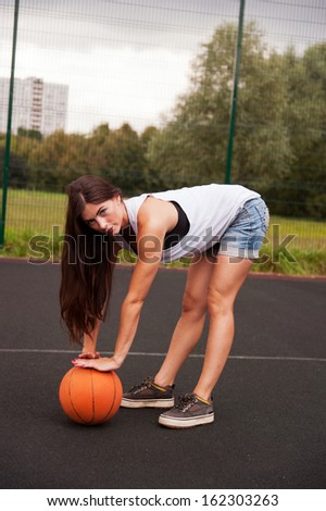Sexy Woman Holding Basketball In Hand On Sports Playground