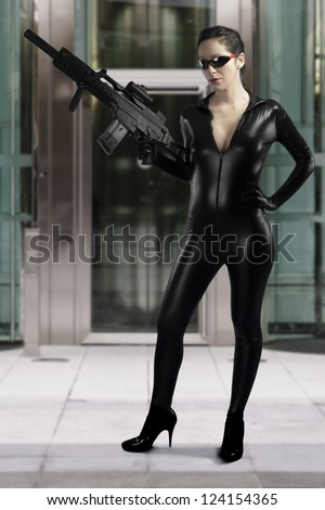 Sexy woman holding gun wearing a black leather dress