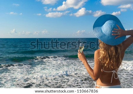 Sexy woman in bikini and hat with glass of wine looking at the sea. Crete. Greece
