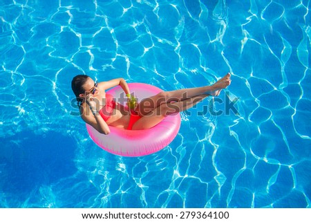 Sexy woman in bikini enjoying summer sun and tanning during holidays in pool with cocktail. Top view. Woman in swimming pool. Sexy woman in bikini.