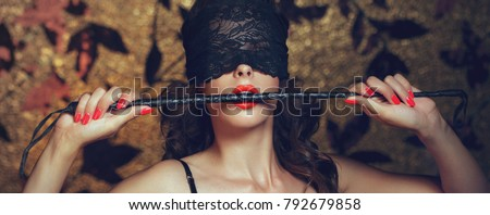 Sexy woman in blindfold bite whip with red lips banner, lace eye cover, bdsm