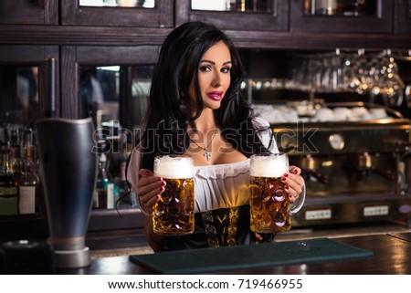 Sexy woman in dirndl dress holding Oktoberfest beer stein. #719466955