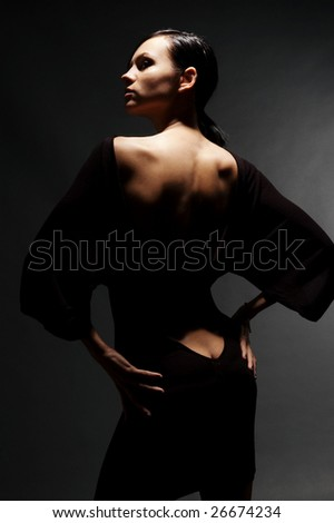 sexy woman in dress with naked back against dark background