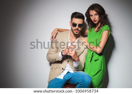 sexy woman in green dress embraces her seated man against grey studio wall