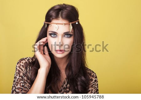 Sexy woman in headband looking at the camera with a sultry look and wearing an animal print top